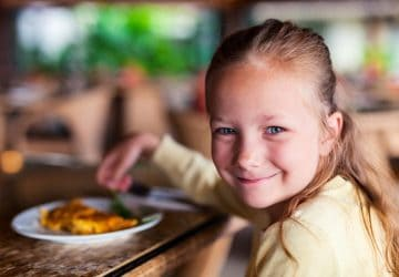 Casual portrait of adorable little girl enjoying meal at restaurant