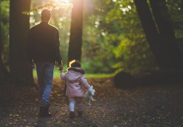 father and daughter walking through wooded area
