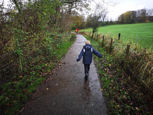 young child running along a walking trail