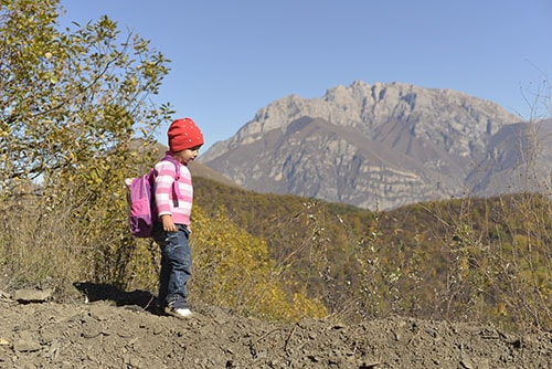 Children hiking with little backpack on