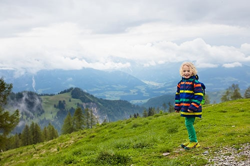 Children hiking in Alps mountains. Kids look at snow covered mountain in Austria. Spring family vacation. Little boy on hike trail in blooming alpine meadow. Outdoor fun and healthy activity.