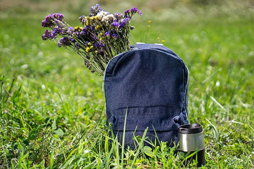 Relaxation and summer hiking concept. Blue jeans school backpack standing on green grass with travel mug near it and beautiful meadow flowers inside it