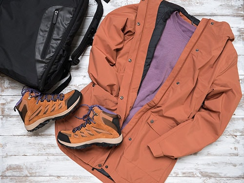 Womens outwear, footwear (brown trench jacket, shuede hiking boots), backpack. Outfit for traveling. Autumn winter collection. Fashion Shopping concept. Flat lay, view from above